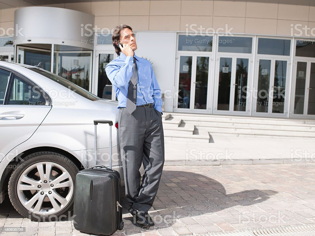 Businessman with suitcase talking on cell phone stock photo