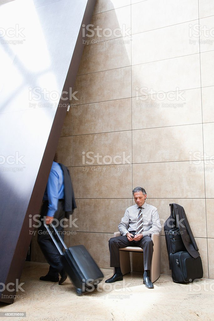 Businessman with suitcase using cell phone stock photo