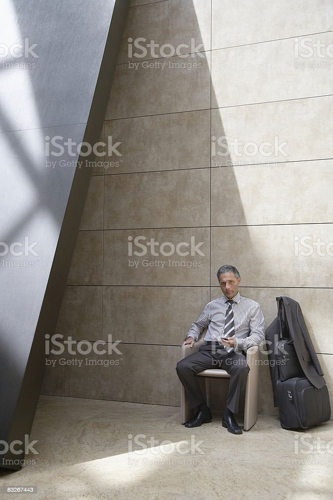 Businessman with suitcase using cell phone royalty-free stock photo