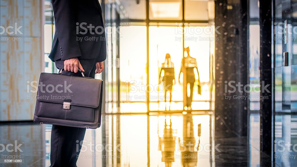 Businessman with suitcase waiting in the lobby stock photo