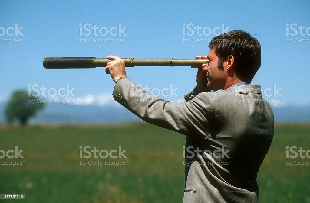 Businessman with telescope in open field royalty-free stock photo