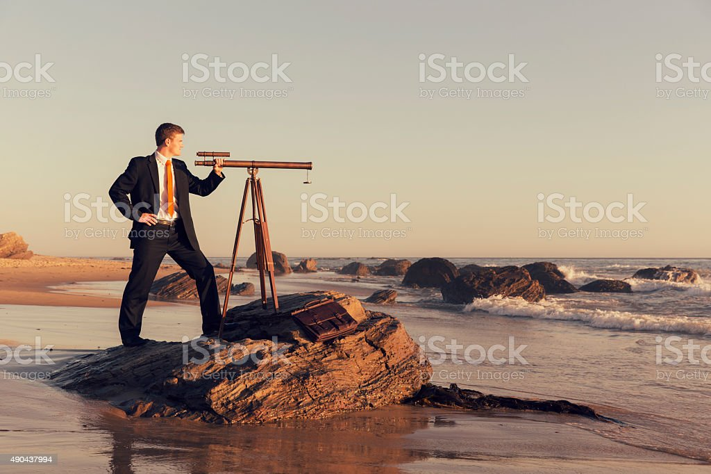 Businessman with Telescope on California Beach stock photo