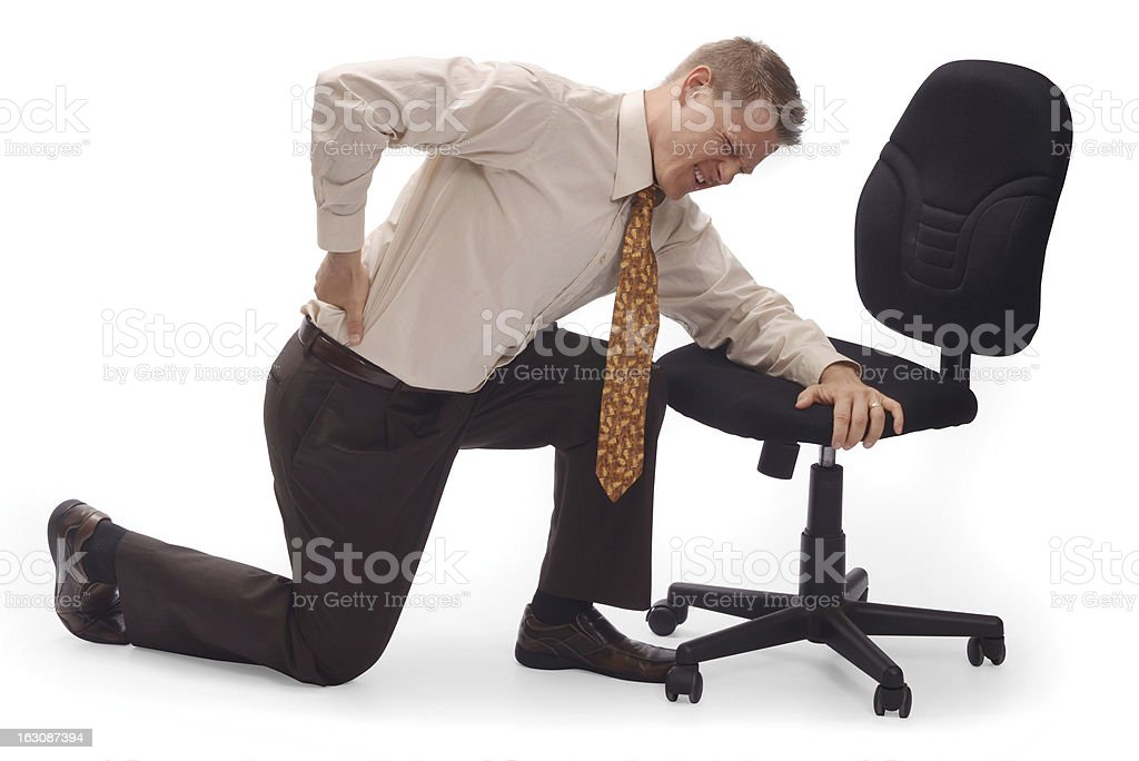 Businessman with the back pain kneeling over a chair stock photo