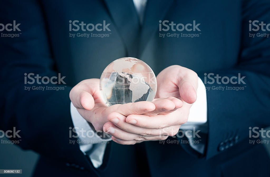 Businessman with the world glass globe in her hands stock photo