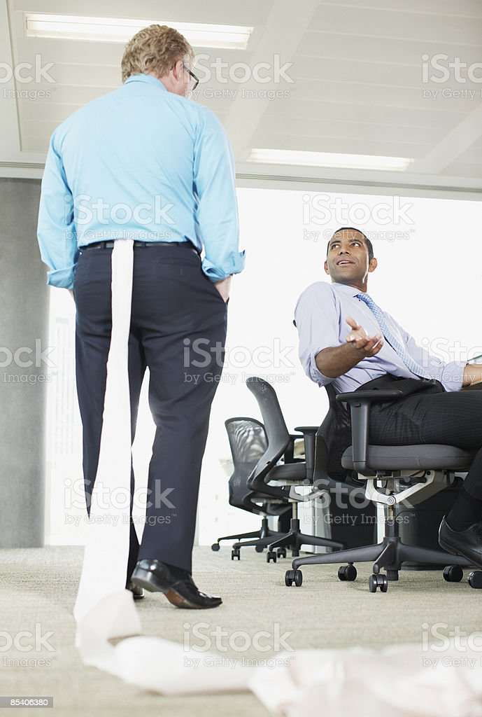 Businessman with toilet paper stuck in his pants stock photo