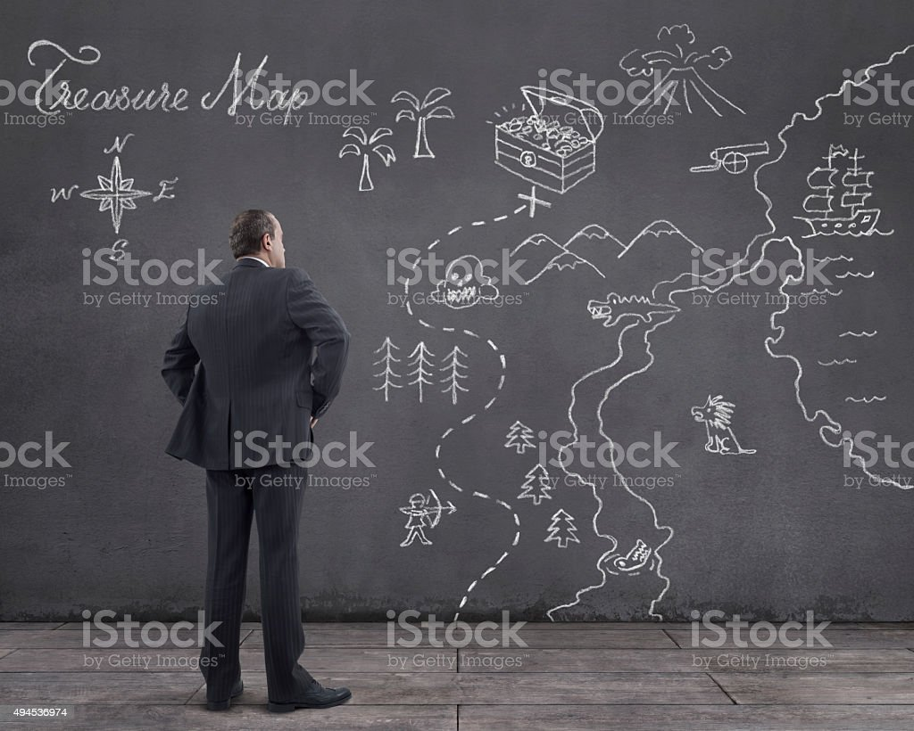 Businessman with Treasure Map Sketched on the Wall stock photo