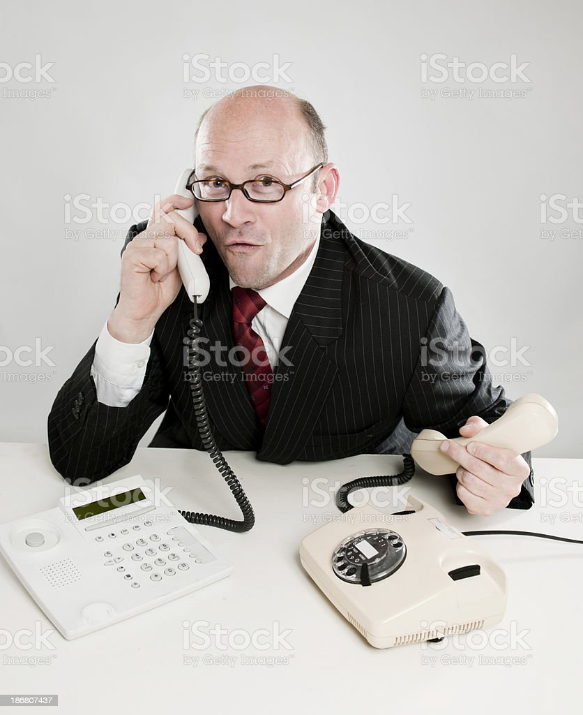 Businessman with two phones stock photo