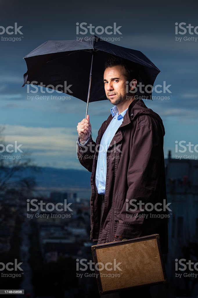 Businessman with Umbrella and Small Briefcase stock photo