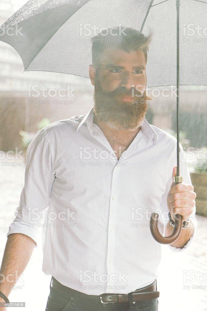 Businessman With Umbrella In The Rain stock photo