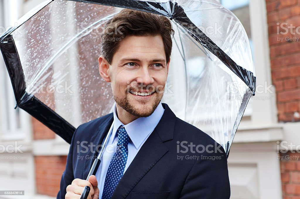 Businessman with umbrella, looking away stock photo