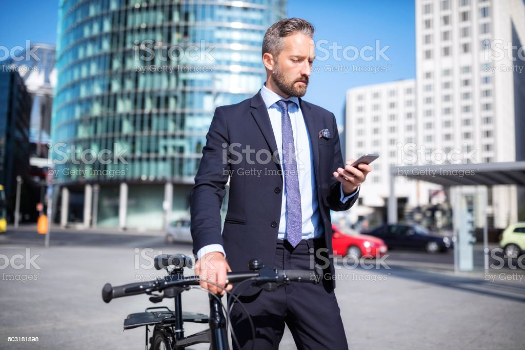 Businessman with with smart phone and bicycle stock photo