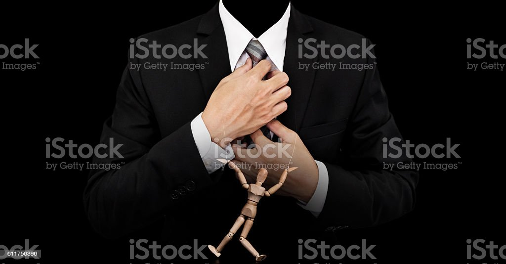 Businessman with wooden figure puppet, concept of business manipulation stock photo