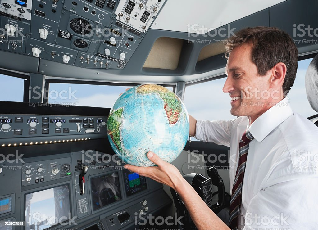 Businessman with world globe in airplane cockpit stock photo