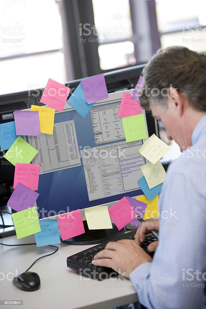 Businessman working at computer covered in reminder notes royalty-free stock photo