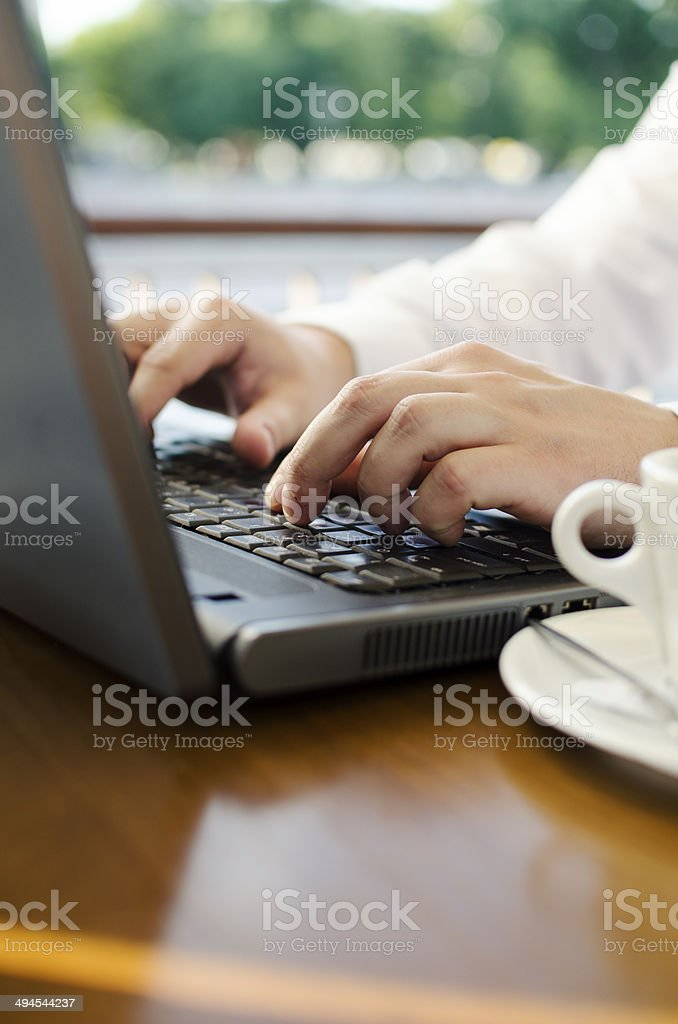 Businessman working at computer sitting at cafe in the city stock photo