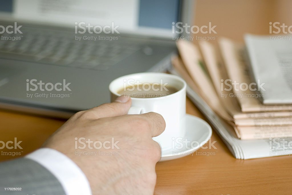 Businessman working at laptop and drinking coffee royalty-free stock photo