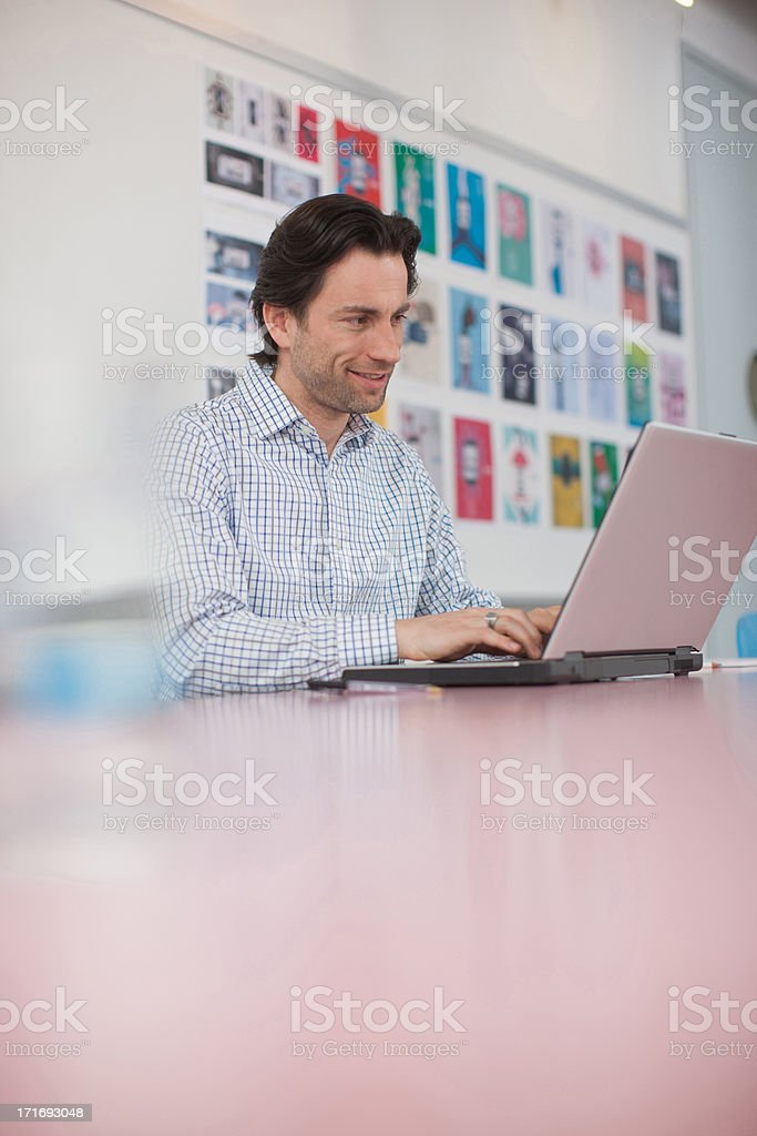 Businessman working at laptop in office stock photo