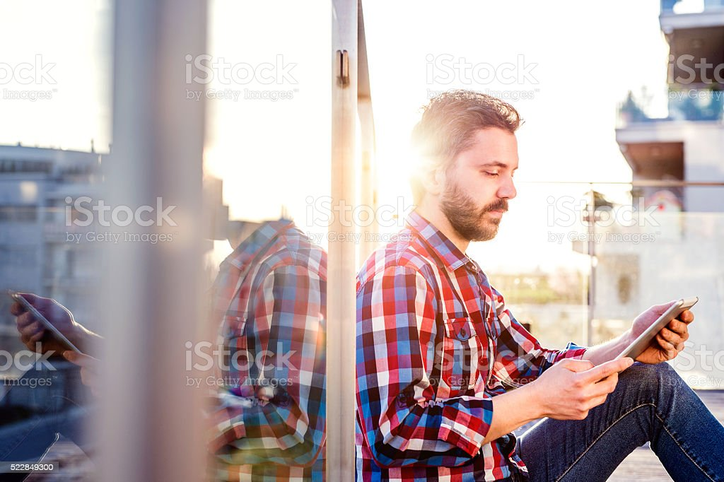 Businessman working from home on tablet, sitting on balcony stock photo
