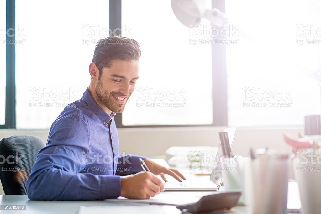 Businessman working in brightly lit office stock photo
