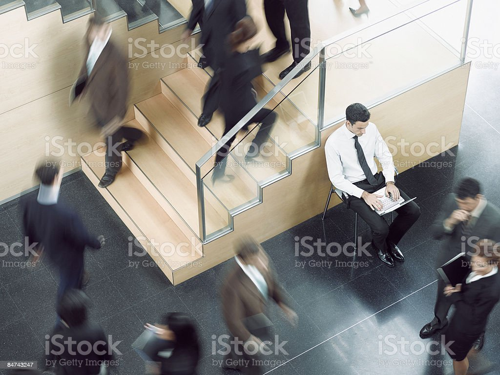 Businessman working in busy office corridor stock photo