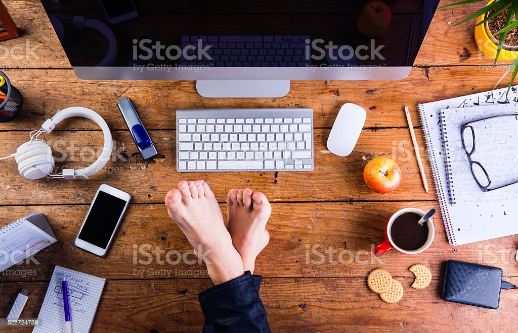 Businessman working in his office with feet on desk stock photo
