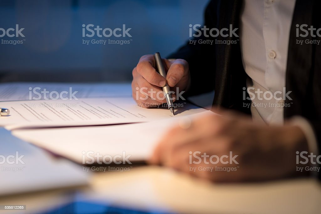 Businessman working late signing a document or contract stock photo