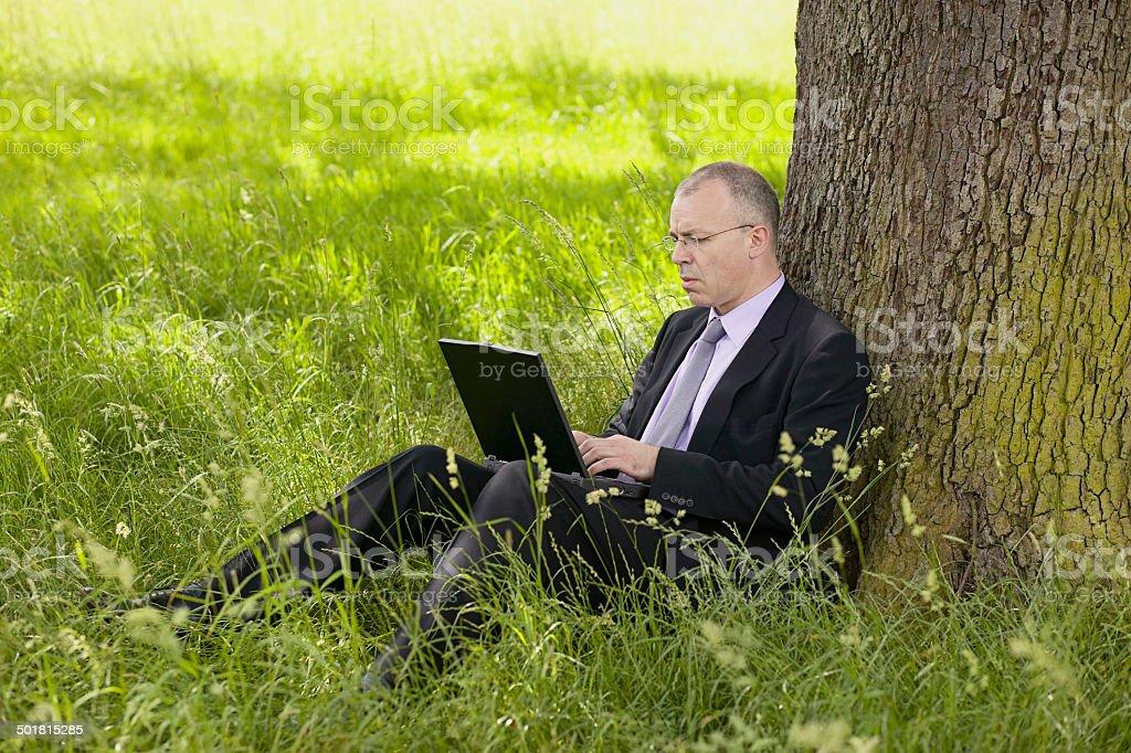 Homme d'affaires travaillant sur un ordinateur à l'extérieur photo libre de droits