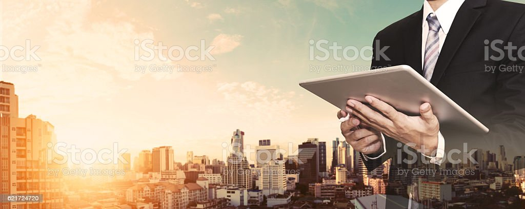 Businessman working on digital tablet outdoor, and city panoramic background stock photo