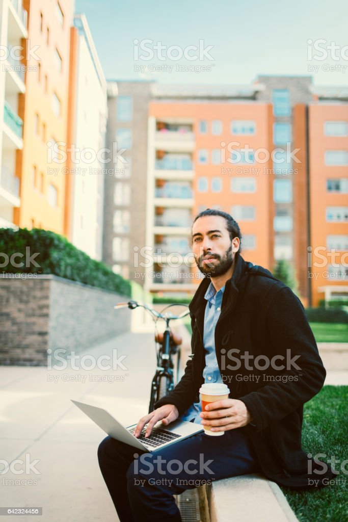 Businessman working on laptop and drinking coffee outdoors stock photo