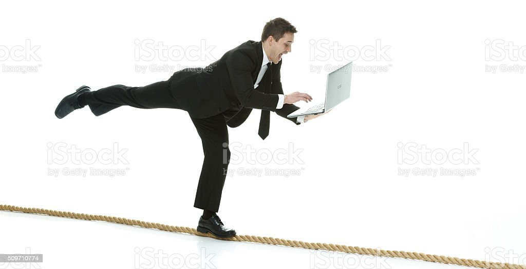 Businessman working on laptop and falling stock photo