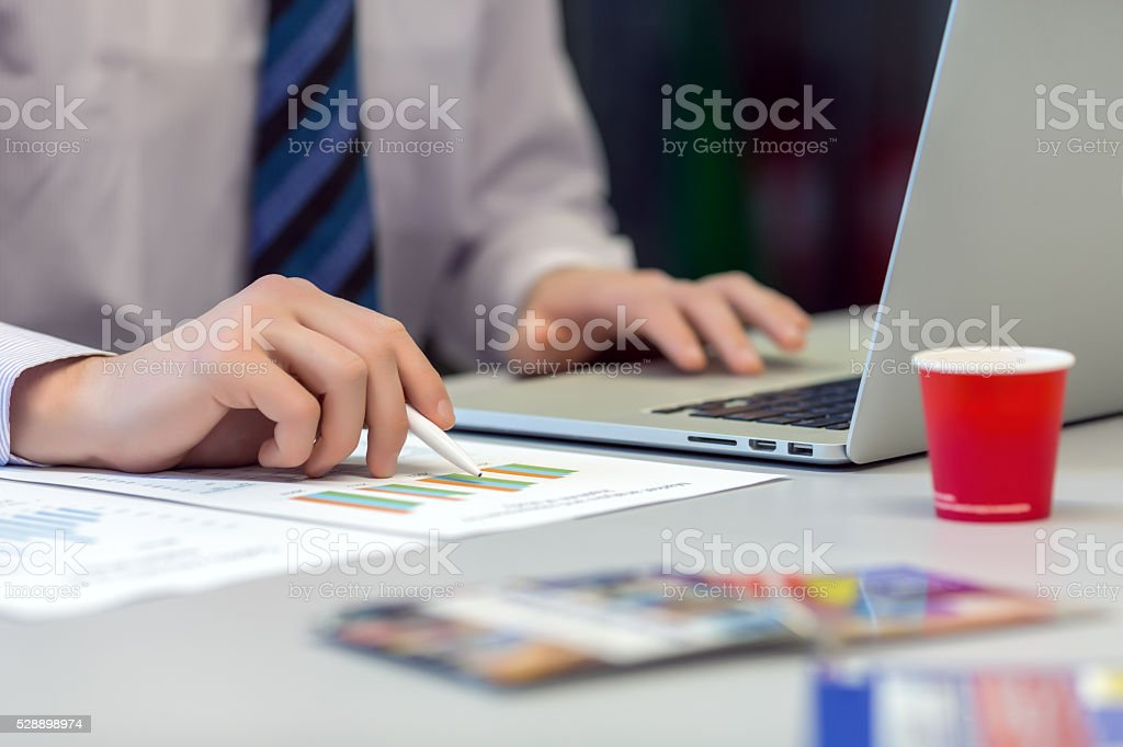 Businessman working on Laptop and printed Charts stock photo