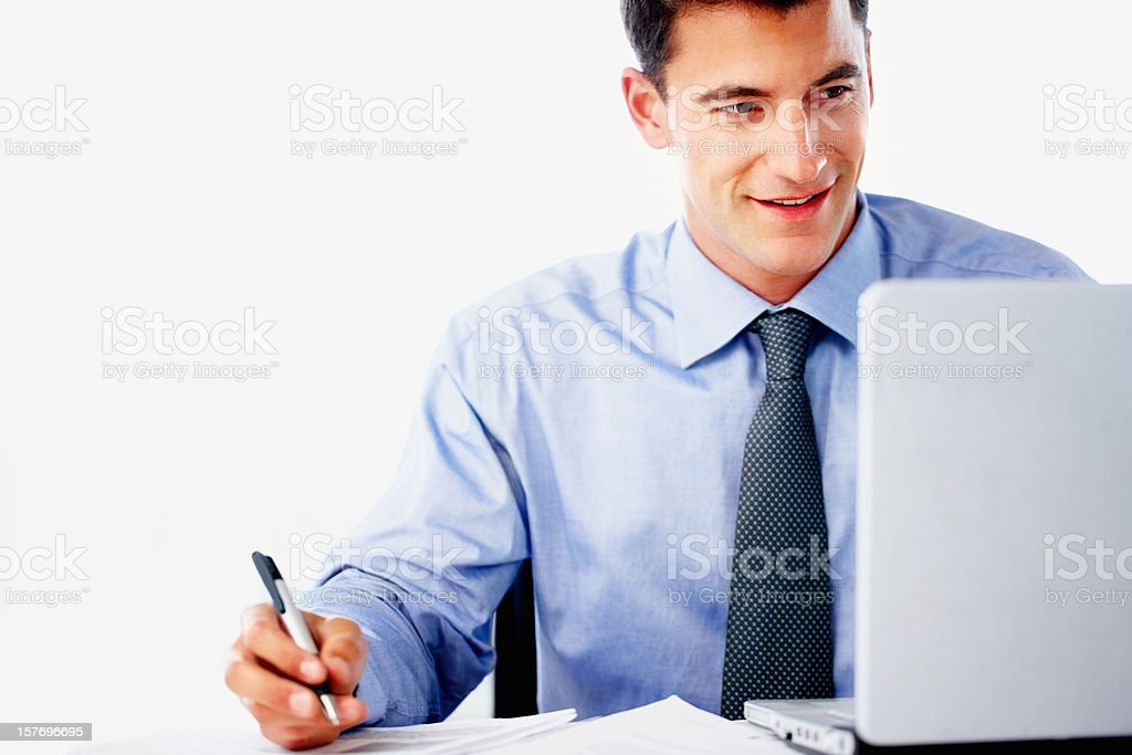 Businessman working on laptop and writing something down royalty-free stock photo