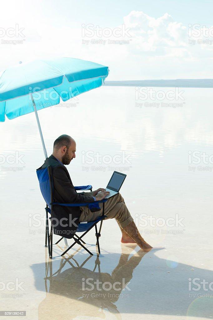 Businessman working on laptop at salt lake. stock photo