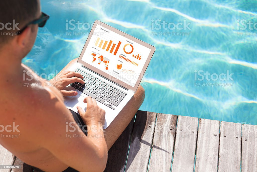 Businessman working on laptop by the pool stock photo