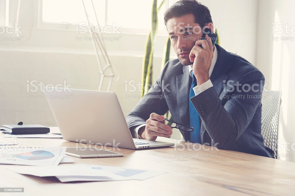 Businessman working on laptop computer and mobile phone. stock photo