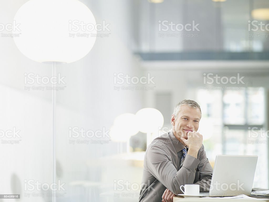 Businessman working on laptop in cafe stock photo