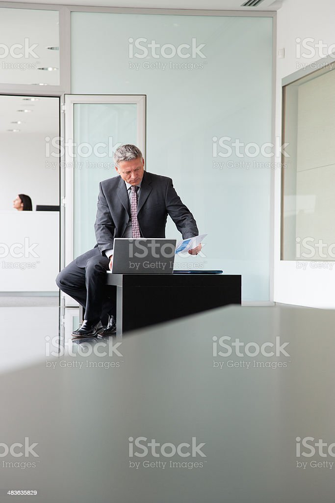 Businessman working on laptop in lobby stock photo