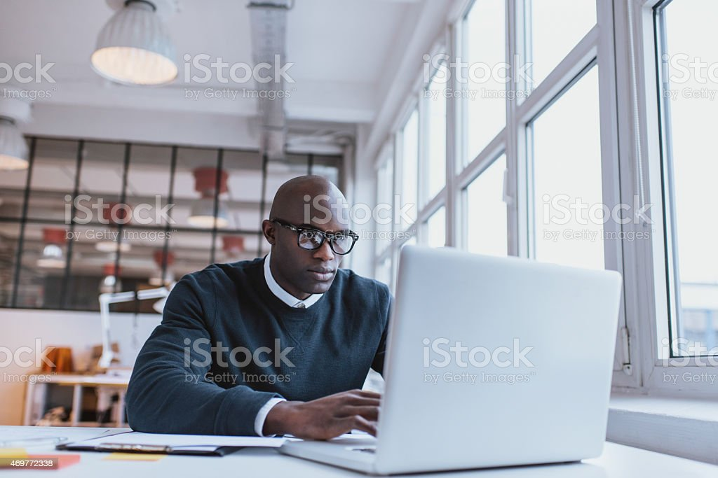 Businessman working on laptop in office stock photo