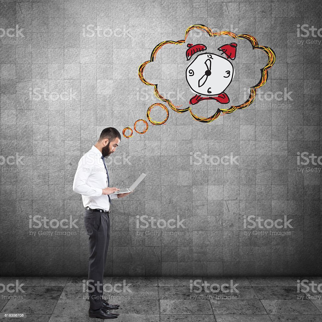 Businessman working on laptop with clock stock photo