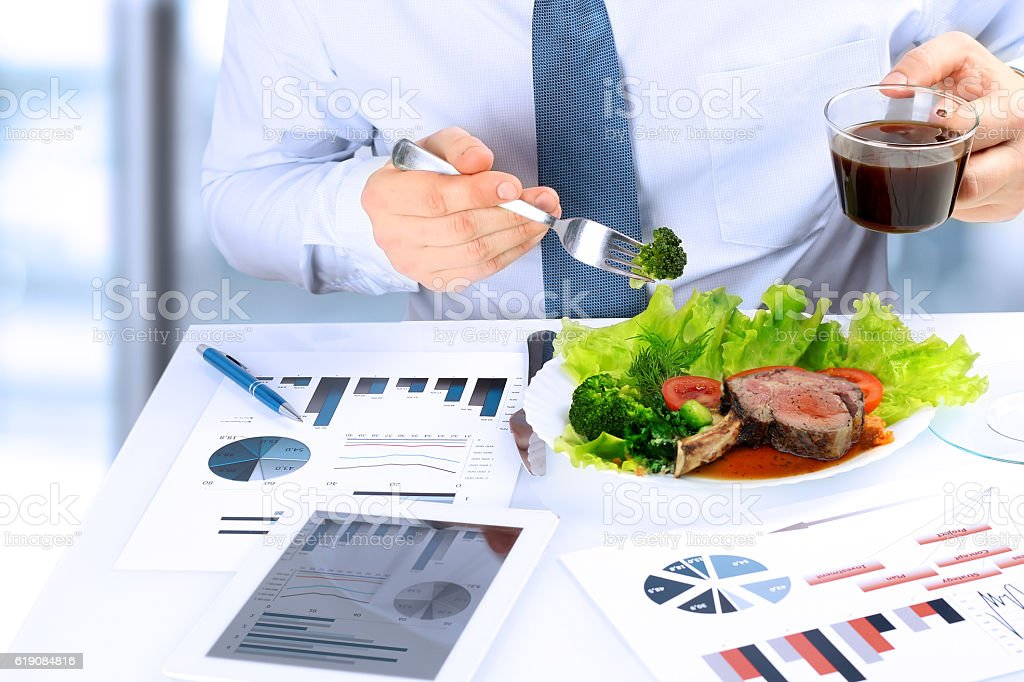 Businessman working on marketing strategy during business lunch, eating steak stock photo