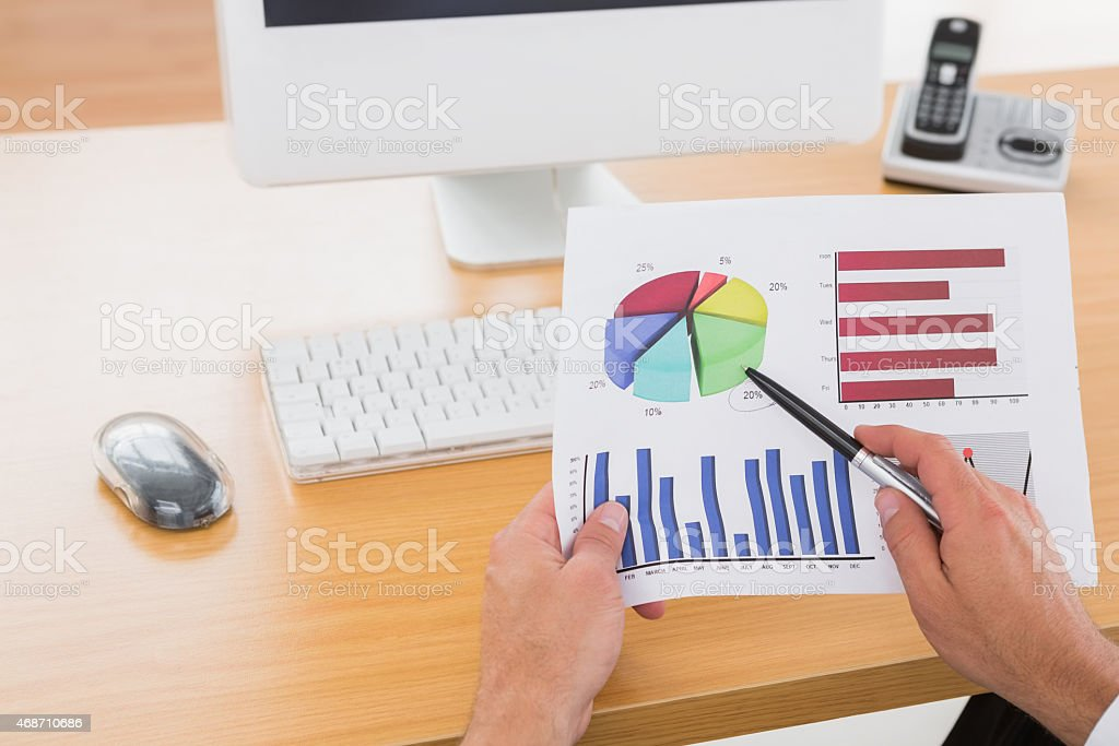 Businessman working on measuring graph at his desk stock photo