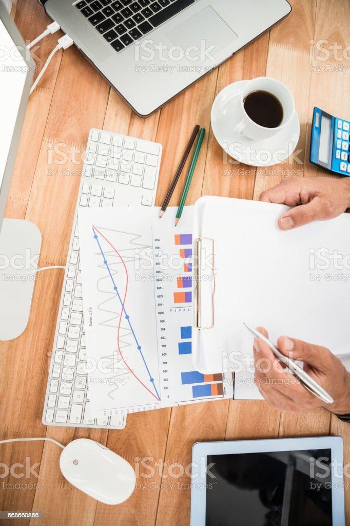 Businessman working on wooden desk stock photo