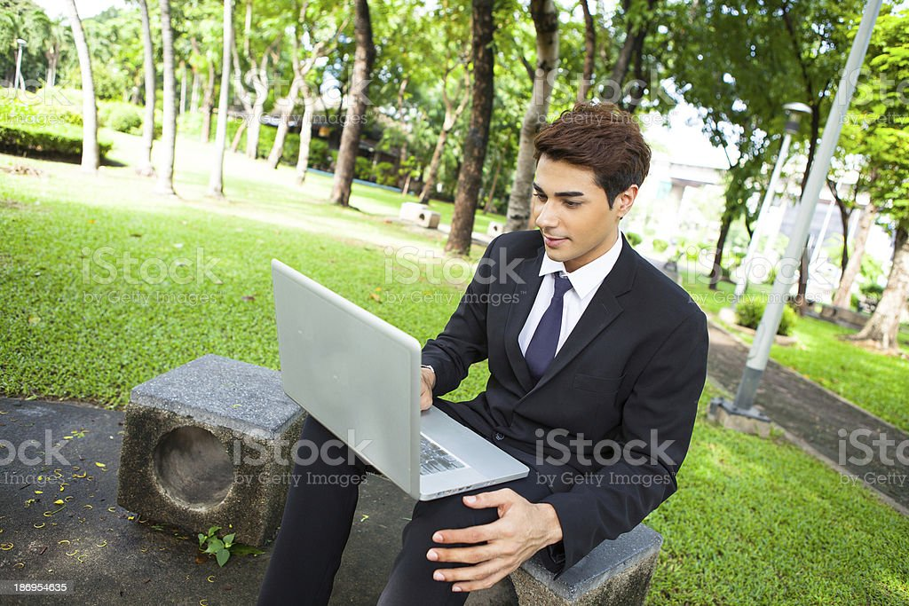 Businessman working outdoors with laptop at the park. royalty-free stock photo