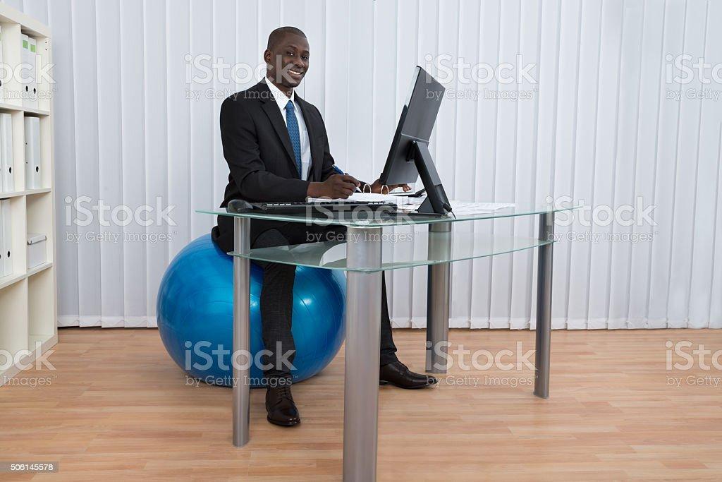Businessman Working Sitting On Pilates Ball stock photo