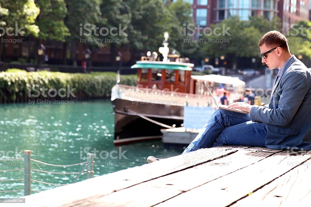 businessman working  with a laptop, sitting, near with river stock photo