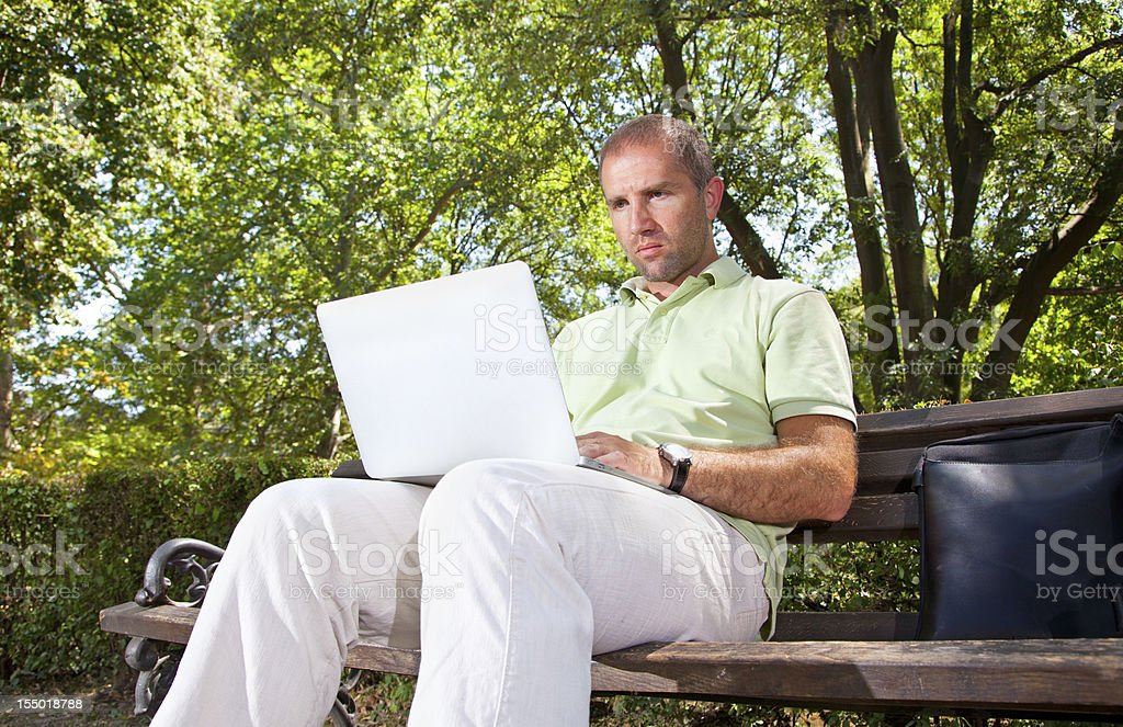 Businessman working with a laptop while sitting in park royalty-free stock photo