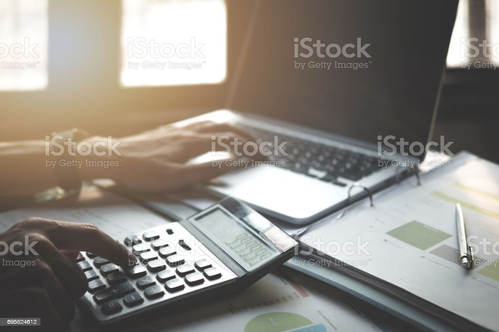 Businessman working with calculator, business document and laptop computer notebook, vintage tone stock photo