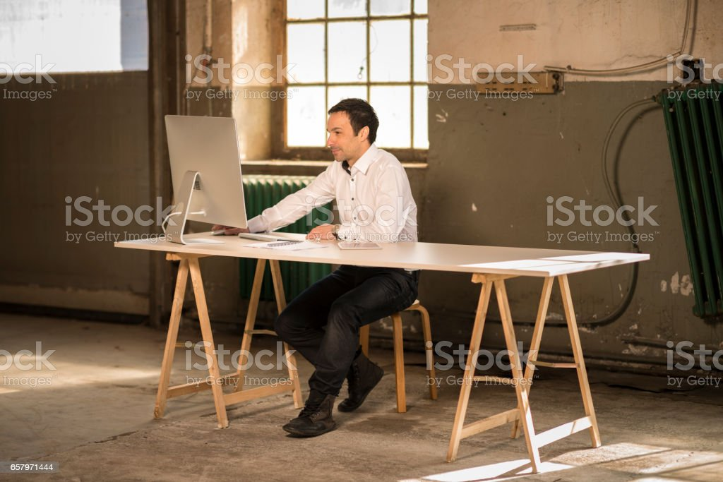 businessman working with computer in old factory stock photo