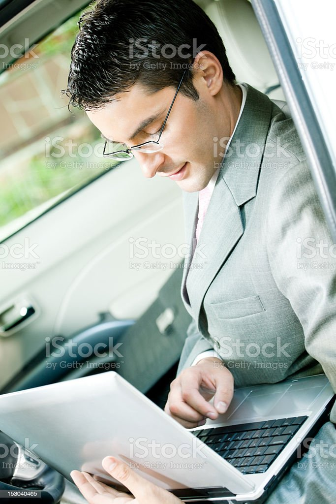 Businessman working with laptop in the car royalty-free stock photo