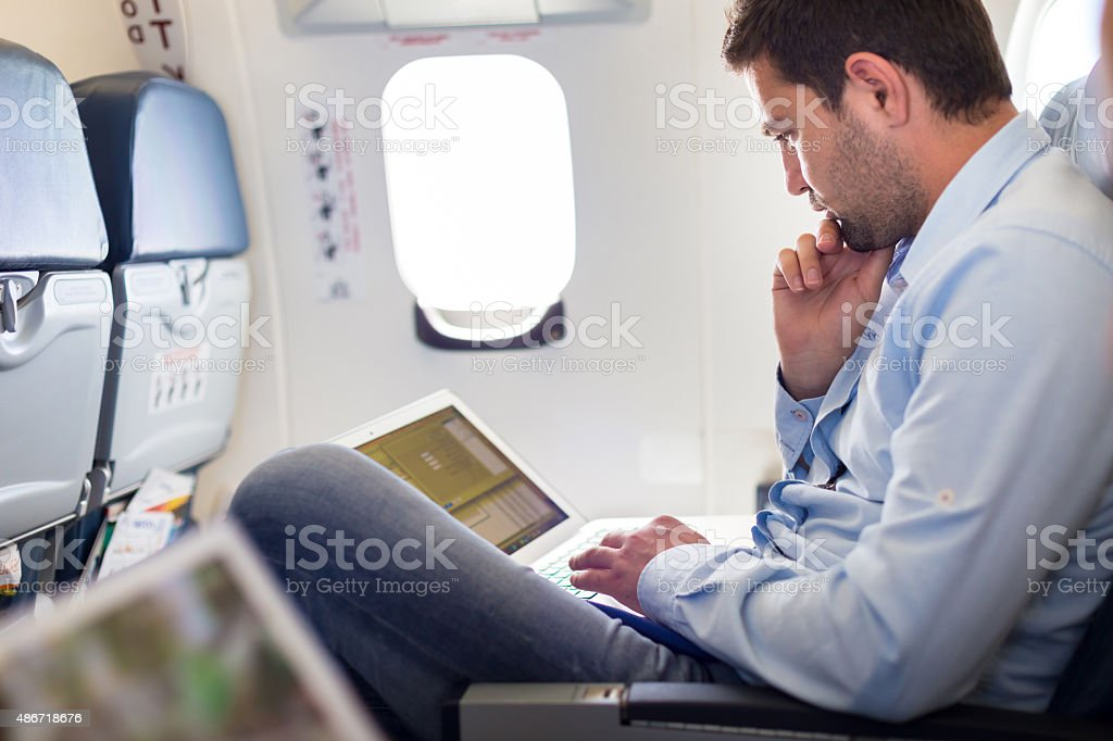 Businessman working with laptop on airplane. stock photo